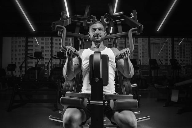 Knappe jongeman pompt zijn schouders in een speciale machine. fitness en bodybuilding concept.
