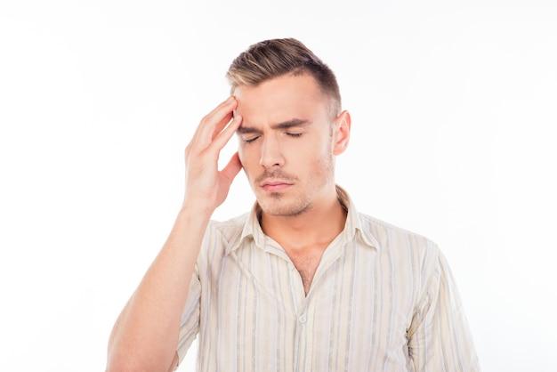 Knappe jongeman raakt zijn hoofd aan met één hand die sterke hoofdpijn voelt