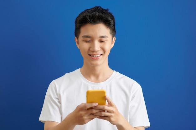 Knappe jongeman sms-berichten verzenden met is mobiele telefoon,