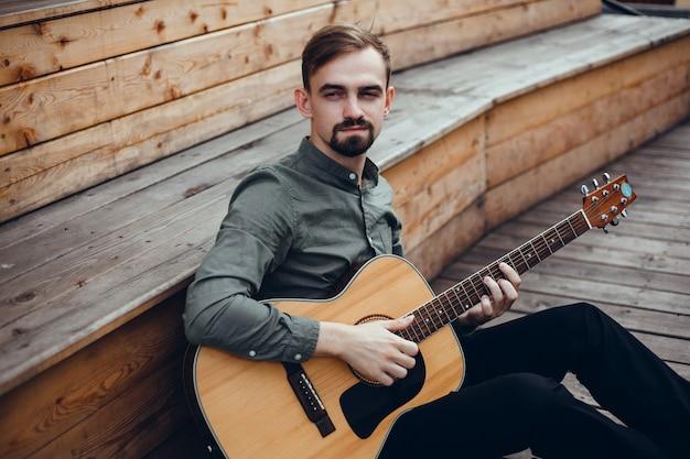 Knappe jongeman speelt gitaar, pakt een snaar, straatmuzikant