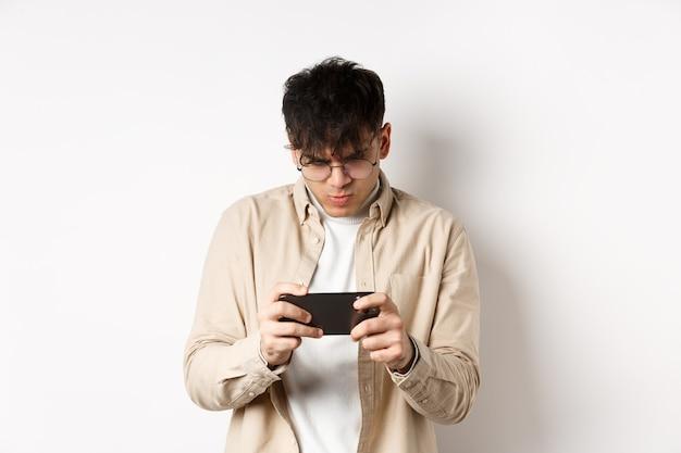 Knappe jongeman staren naar mobiel scherm en spelen van videogame op smartphone, staande op een witte muur. kopieer ruimte