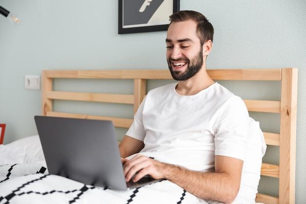 Knappe jongeman tot in bed, die op laptop computer werkt