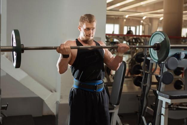 Knappe jongeman trainen met een halter in de sportschool