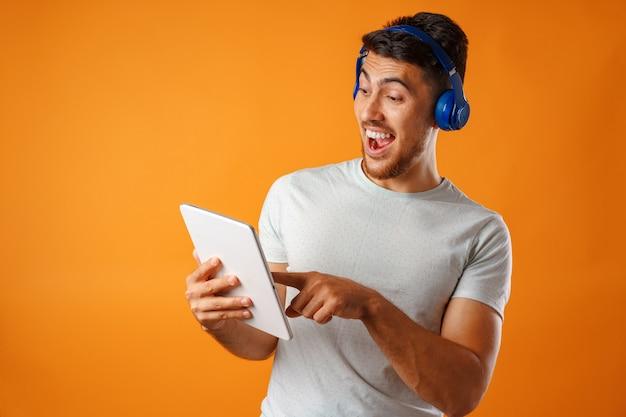 Knappe jongeman van gemengd ras, luisteren naar muziek met blauwe koptelefoon
