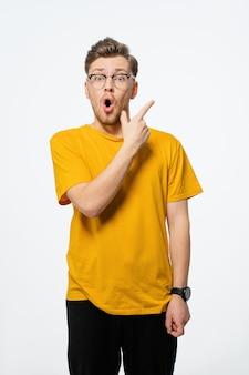 Knappe jongeman wijzende vinger zijwaarts in bril geschokt met een verbaasde uitdrukking op zijn gezicht