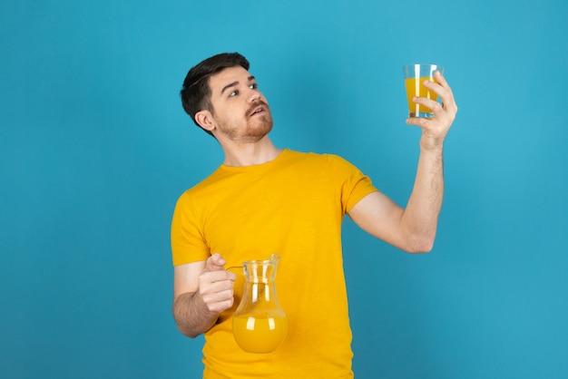Knappe jongen die een glas sinaasappelsap vasthoudt en ernaar kijkt.