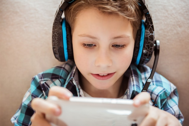 Knappe jongen die met hoofdtelefoons tablet speelt. detailopname