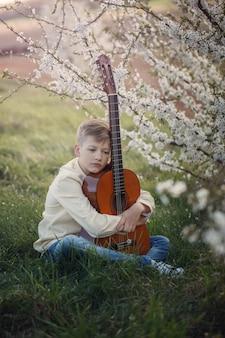 Knappe jongen die muziek maakt die de gitaarzitting op het gras in de zomerdag speelt.