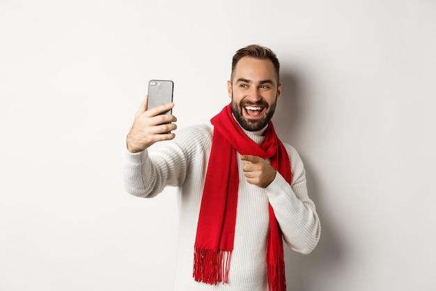 Knappe jongen die vrolijk kerstfeest wenst op videogesprek, hand zwaait naar mobiele telefoon en glimlacht, staande in trui met rode sjaal, witte achtergrond