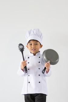 Knappe jongen in chef-kok eenvormig op geïsoleerd wit Premium Foto