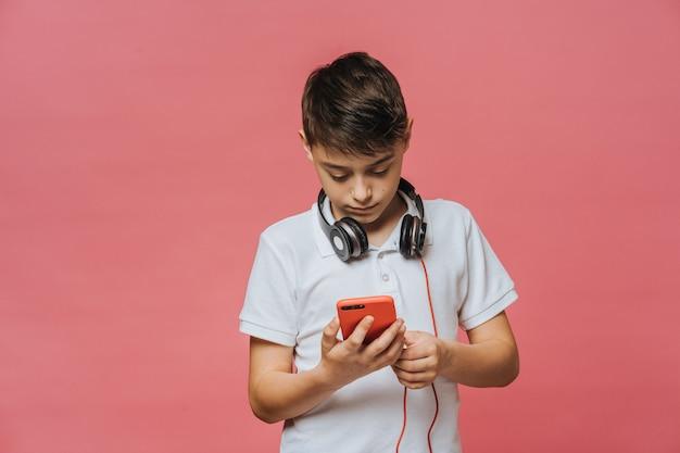 Knappe jongen in een wit t-shirt en een koptelefoon op zijn nek, houdt zijn smartphone, op zoek naar nieuwe muziek op het internet. jeugd en hedendaagse mensen concept.