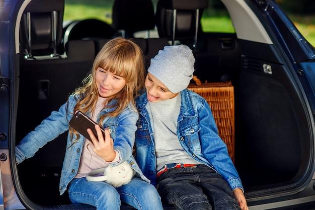 Knappe jongen in hoed en mooi meisje met blond lang haar dat foto's neemt