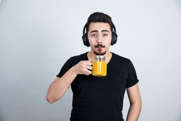 Knappe jongen in koptelefoon drinken uit glazen beker met sinaasappelsap.