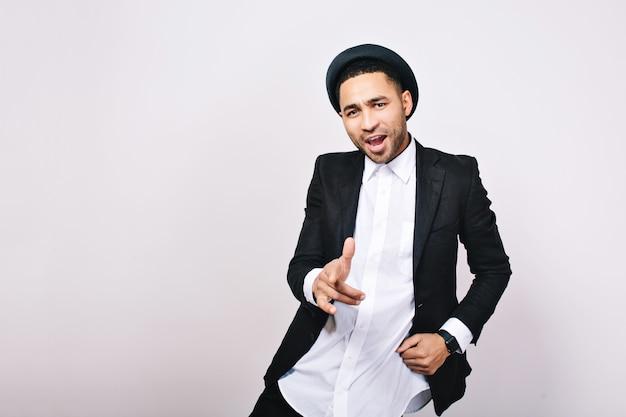 Knappe jongen in pak, hoed dansen en zingen. modieuze kantoormedewerker, succes, zakenman