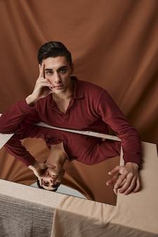 Knappe jongen in shirt poseren aan een tafel binnenshuis op de achtergrond van een stof. hoge kwaliteit foto