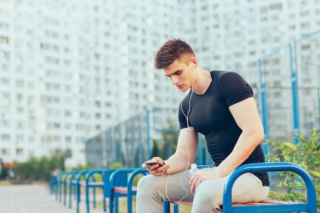 Knappe jongen in sport zwart t-shirt en grijze sportbroek zit op bankje op de achtergrond van de stad en het stadion. hij typt op de telefoon en luistert naar muziek via een koptelefoon.