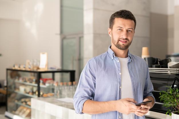 Knappe jongen in vrijetijdskleding scrollen in smartphone terwijl op zoek naar jou in café