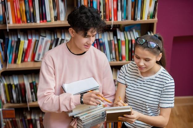 Knappe jongen in vrijetijdskleding wijzend op notities van zijn klasgenoot terwijl zowel een van de punten van de thuistaak in de bibliotheek bespreken