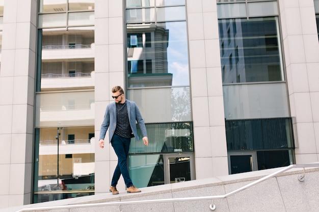 Knappe jongen in zonnebril wandelen op straat