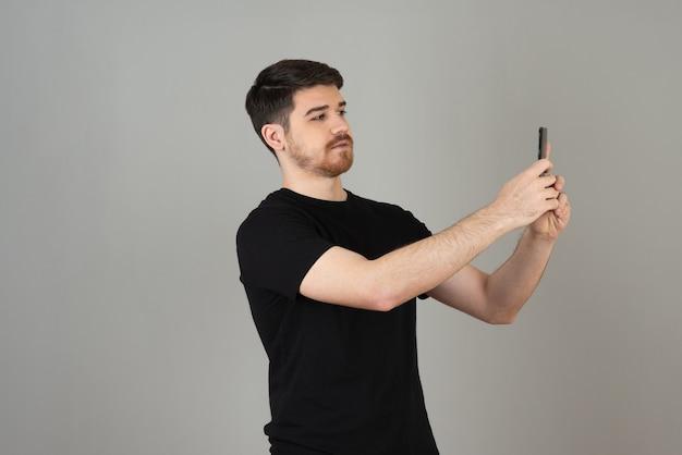 Knappe jongen in zwart t-shirt selfie te nemen op een grijs.