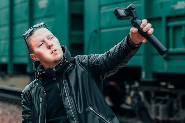 Knappe jongen in zwarte kleding en zonnebril selfie maken of streaming video met actiecamera met gimbal camerastabilisator bij spoorweg