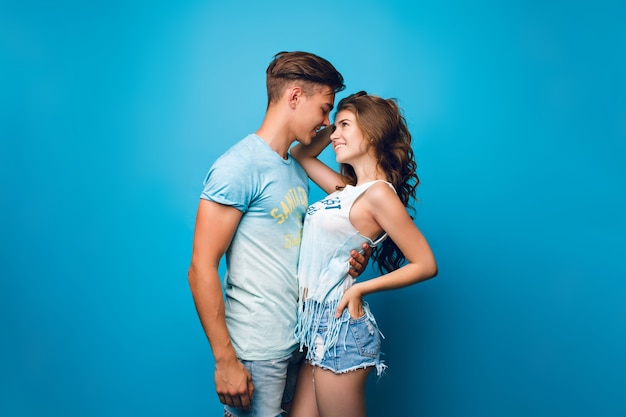 Knappe jongen knuffelt mooi meisje met lang haar op blauwe achtergrond in de studio. ze draagt een wit t-shirt, korte broek en kijkt hem aan.