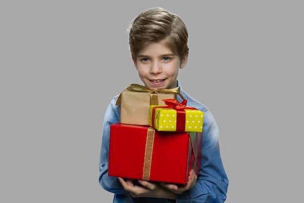 Knappe jongen kreeg verjaardagscadeautjes. gelukkig lachend kind met stapel geschenkdozen op grijze achtergrond, vooraanzicht.