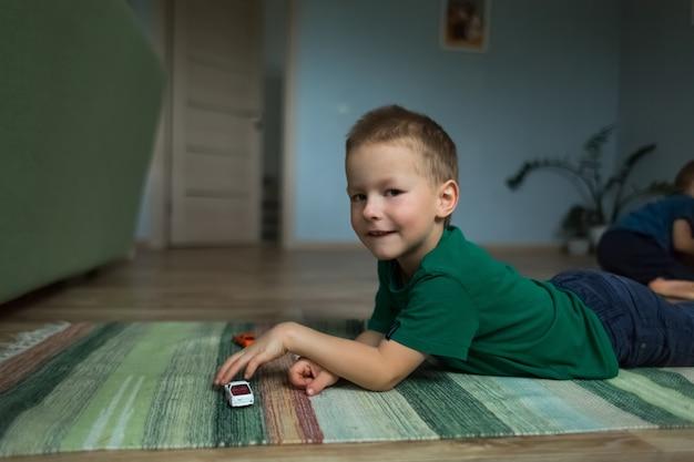 Knappe jongen liggend op de vloer op het tapijt speelt met speelgoedauto's.