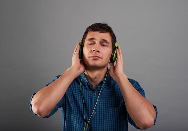 Knappe jongen luistert naar muziek met gesloten ogen