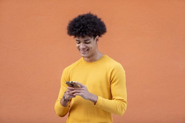Knappe jongen met afro kapsel op zoek naar de mobiel