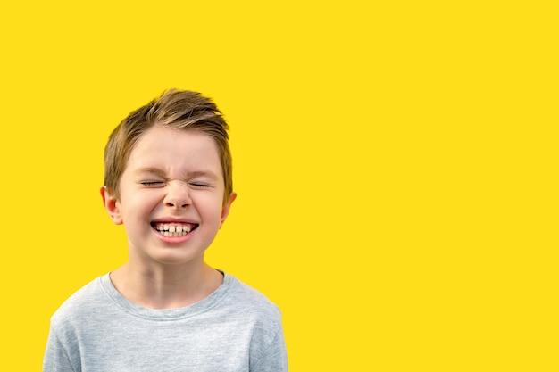 Knappe jongen met dicht verpest zijn ogen en lacht met zijn mond wijd open,