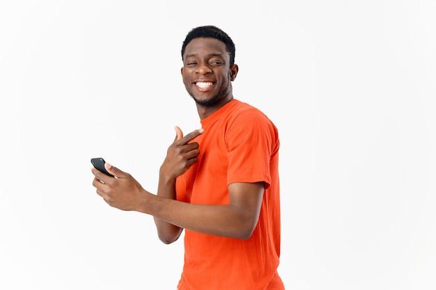 Knappe jongen met een afrikaans uiterlijk lacht en houdt een mobiele telefoon in zijn hand