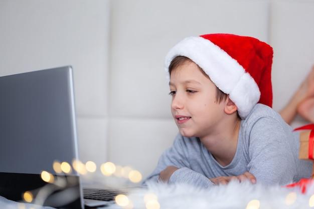 Knappe jongen met een kerstmuts kijkt naar het scherm van de laptop terwijl hij thuis op bed ligt. winter gezellige avond, online brief santa claus, online communicatie met vrienden.
