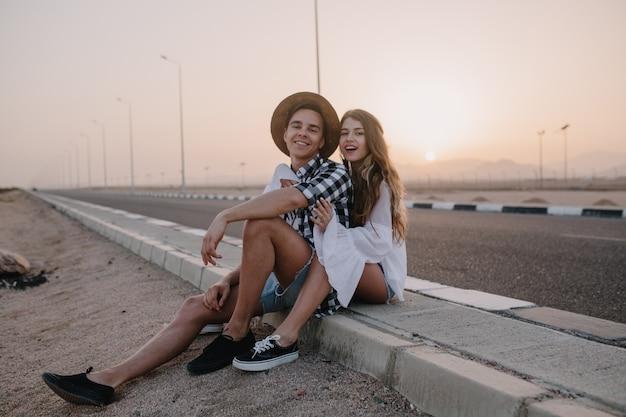 Knappe jongen met hoed en vrouw in witte vintage blouse zitten samen op de weg en geniet van prachtige zonsondergang. charmante langharige jonge vrouw die in de buurt van de snelweg met haar vriendje rust