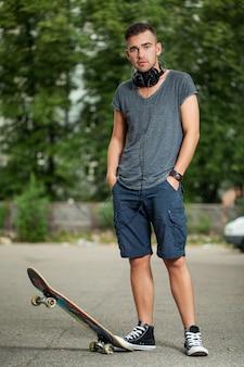 Knappe jongen met koptelefoon en skateboard