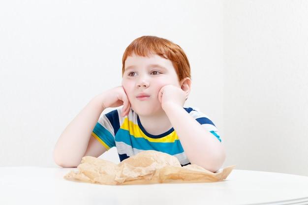 Knappe jongen met rood haar zit aan een lege tafel