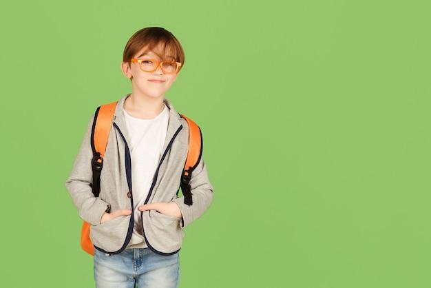 Knappe jongen met rugzak klaar om te studeren. terug naar schoolconcept. schattig schoolkind in glazen over
