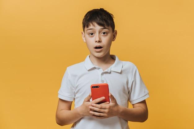 Knappe jongen met smartphone staart naar kijker, voelt zich verrast, opent mond, gekleed in wit t-shirt geïsoleerd over gele muur met lege ruimte voor uw promotie