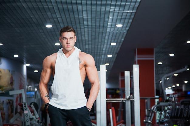 Knappe jongen op fitness gym poseren voor camera