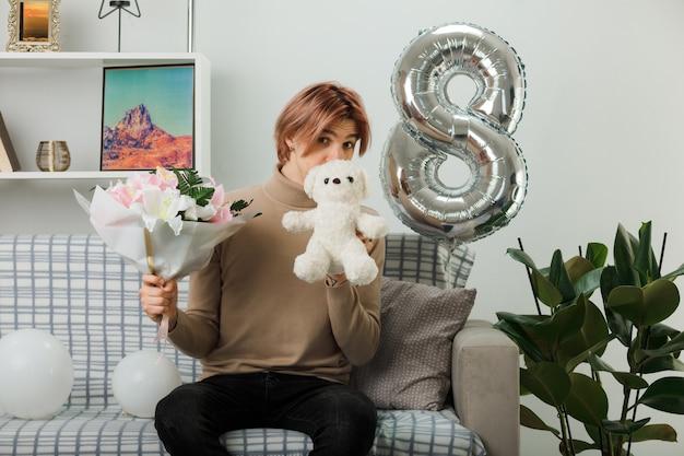Knappe jongen op gelukkige vrouwendag met boeket met teddybeer zittend op de bank in de woonkamer