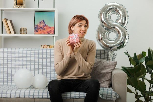 Knappe jongen op gelukkige vrouwendag met cadeau zittend op de bank in de woonkamer