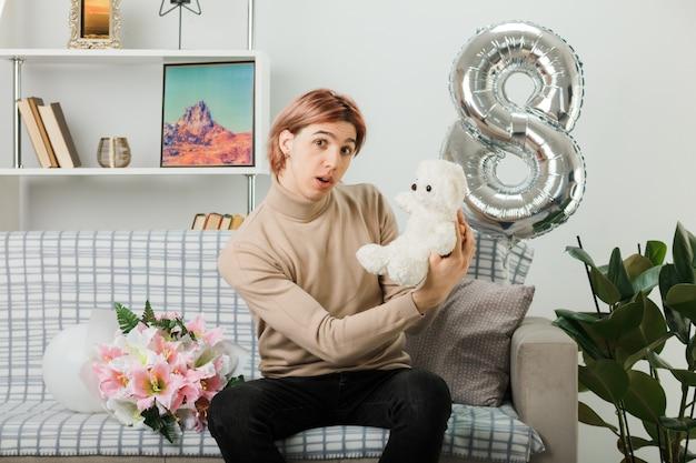 Knappe jongen op gelukkige vrouwendag met teddybeer zittend op de bank in de woonkamer