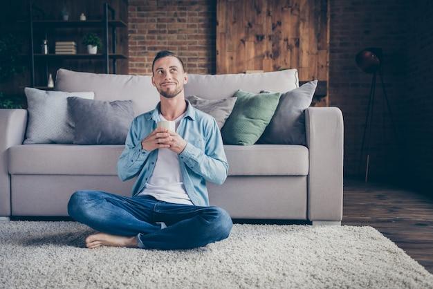 Knappe jongen zit comfortabel pluizig tapijt warme verse koffie drinken