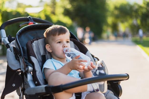 Knappe jongen zit in een wandelwagen en drinkt water uit een fles op een warme zomerdag
