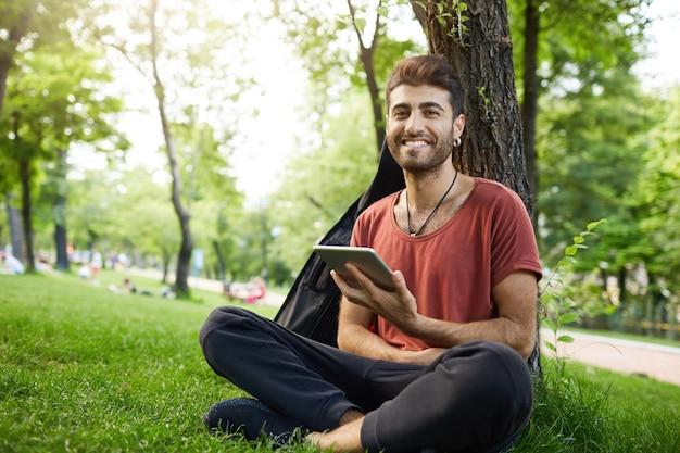 Knappe jongen zit in parkgras, leest een digitaal tabletboek, sluit wifi aan en kijkt naar sociale media