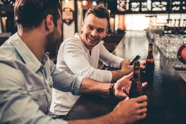 Knappe jongens praten en glimlachen tijdens het rusten in de pub.
