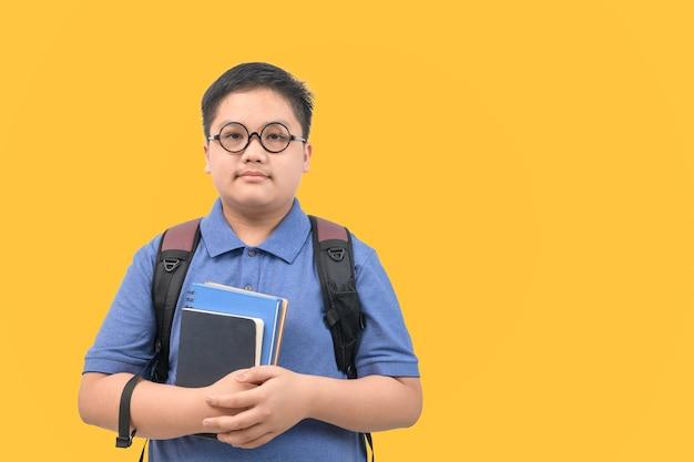 Knappe jongensstudent die een schooltas draagt en een boek houdt