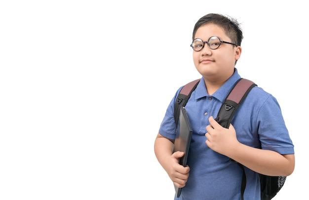 Knappe jongensstudent die een schooltas en een laptop draagt