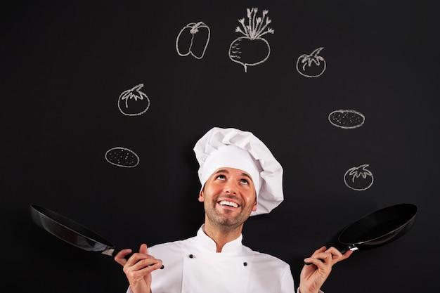 Knappe jongleur van de chef met groente
