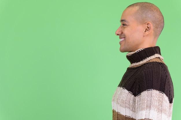 Knappe kale multi-etnische man klaar voor de winter tegen groene muur